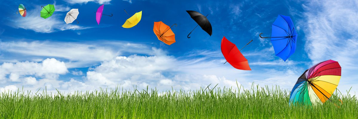 flying colorful umbrellas on grass in front of blue sky